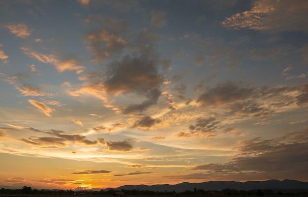 Tramonto variopinto e alba con nuvole. colore arancione della natura. molte nuvole bianche nel cielo. il tempo è sereno oggi. tramonto tra le nuvole. il cielo è crepuscolare.