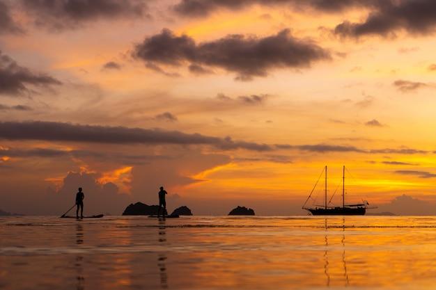 Tramonto colorato su una spiaggia tropicale. tramonto arancione sull'oceano. colorato tramonto ai tropici. un paio di persone nuotano su tavole da sup