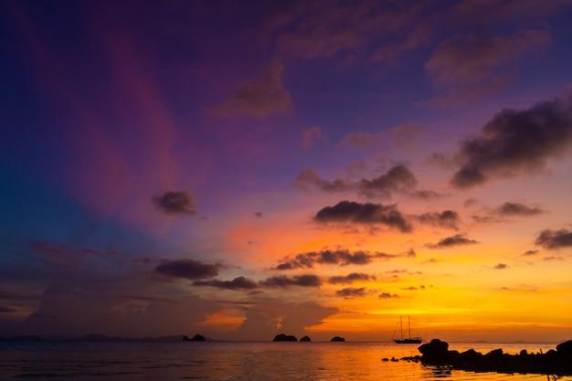 Tramonto colorato su una spiaggia tropicale. tramonto arancione sull'oceano. colorato tramonto ai tropici. nell'acqua c'è una nave a vela. barca a vela profilata con alberi