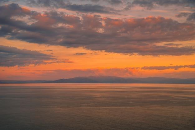 Tramonto colorato con sfondo di cielo drammatico sul mare.
