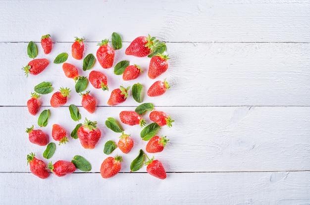 Mix di frutta dolce colorato di fragola e foglie di menta verde sul tavolo in legno bianco wintage. sfondo di frutta brillante.