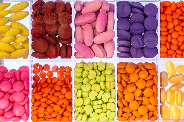 Pillole variopinte delle capsule e delle compresse in una scatola di vetro della dose della medicina