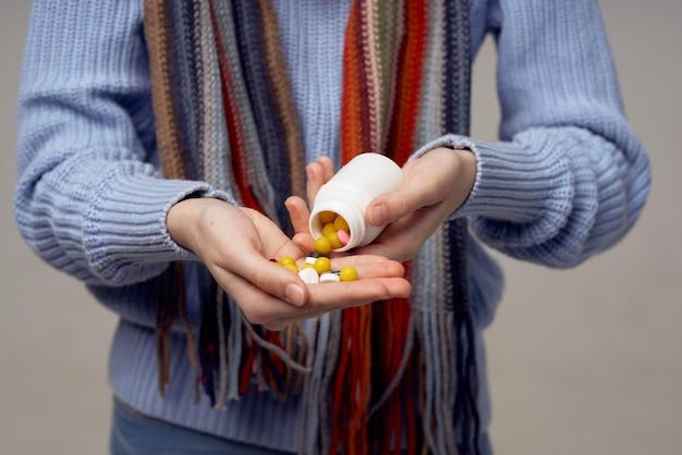 Compresse colorate vitamine in un barattolo mani femminili sciarpa modello maglione. foto di alta qualità