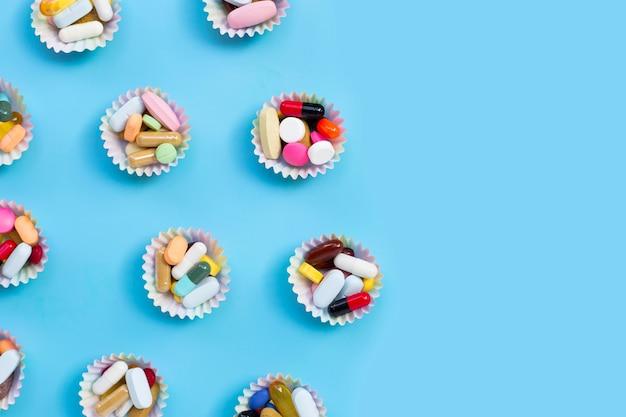 Compresse colorate con capsule e pillole in involucri di cupcake su sfondo blu.