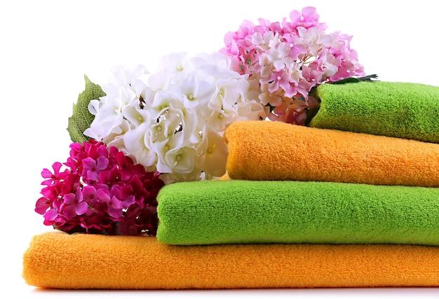 Asciugamani colorati e fiori, isolati su bianco