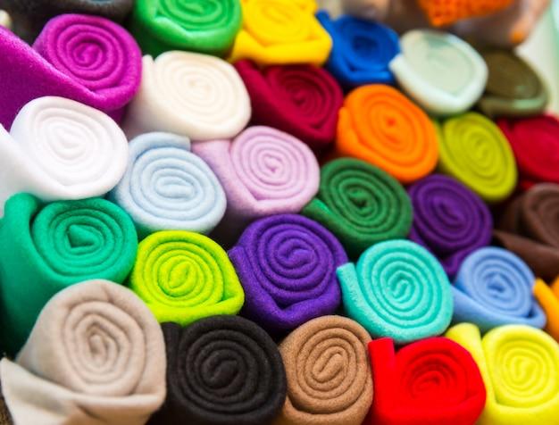 Asciugamani colorati arrotolati in un primo piano del tubo. mensola con tessuto, vetrina negozio