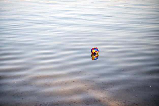 Palla giocattolo colorata, attributo del gioco di calcio che si riflette nell'acqua ondulata blu. sport estivo all'aperto. svago e vacanza. natura e attività