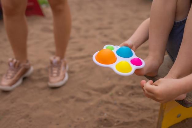 Il giocattolo sensoriale antistress colorato e alla moda si agita spingendolo pop e semplice fossetta nelle mani dei bambini i bambini condividono giocattoli e giocano insieme