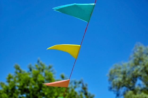 Bandiere di festival di carta triangolare colorate su sfondo blu cielo