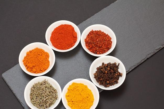 Varie spezie macinate colorate, chiodi di garofano secchi ed erbe aromatiche in ciotole di porcellana su tavola di pietra nera. vista dall'alto.