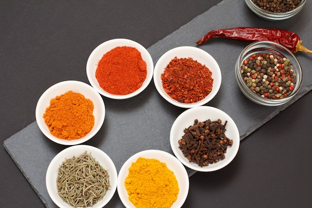 Varie spezie macinate colorate, zafferano, cumino, curry, rosmarino secco e chiodi di garofano in ciotole di porcellana e vetro su tagliere in pietra nera con pepe rosso secco. vista dall'alto.