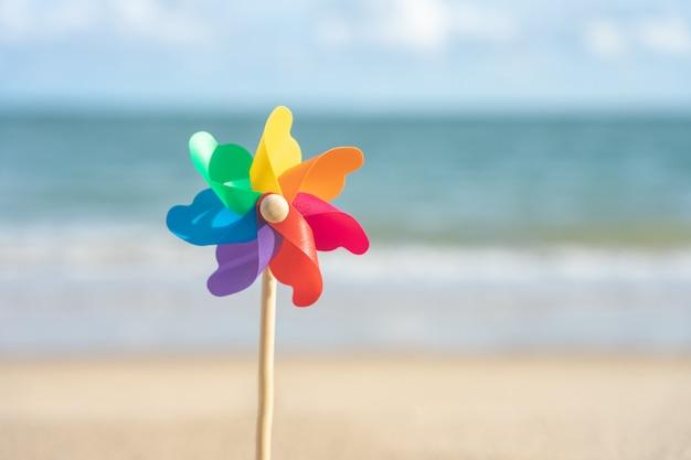 Carta colorata mulino a vento ricamato sulla spiaggia vista mare di giorno