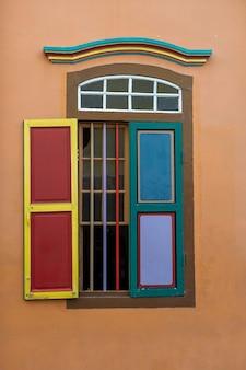 Finestra astratta in legno colorato, primo piano. edificio di architettura in stile coloniale a little india, città di singapore. sfondo e trama di un'architettura luminosa