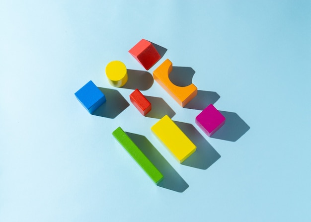 Giocattolo di blocco di legno colorato su sfondo azzurro.