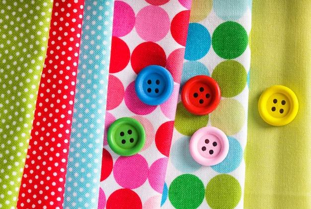 Bottoni in legno colorati sui tessuti, concetto di cucito