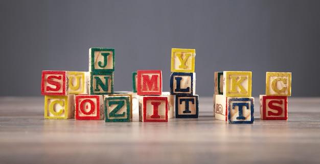 Cubi di legno colorati con lettere sul tavolo di legno.