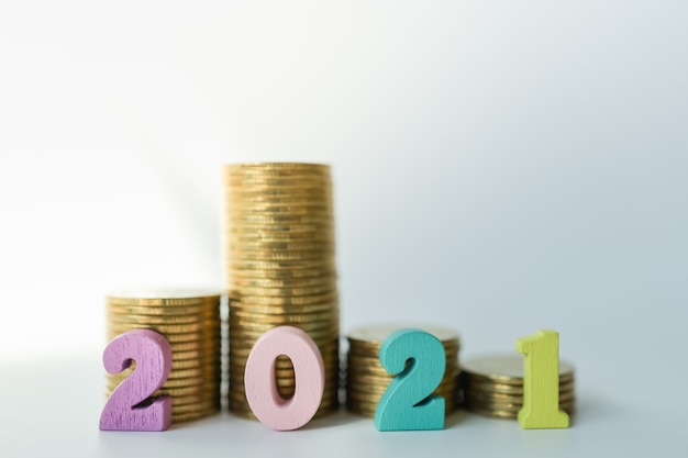 Numero 2021 in legno colorato con pila di monete d'oro.