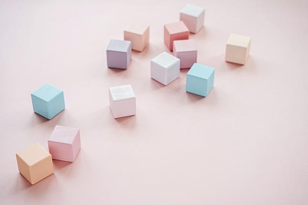 Blocchi giocattolo in legno colorato. alla moda giocattoli per bambini su sfondo rosa pastello. accessori per giocattoli ecologici e privi di plastica per bambini. disposizione piatta, vista dall'alto