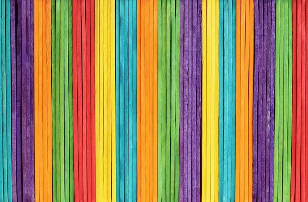 Struttura variopinta della parete in legno nei colori dell'arcobaleno luminoso