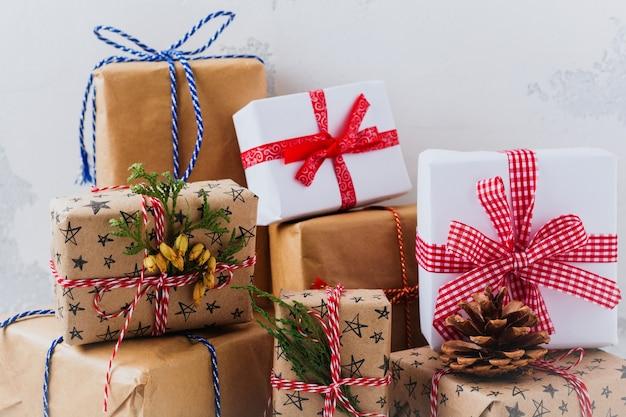 Contenitori di regalo avvolti variopinti con i regali sulla superficie strutturata bianca