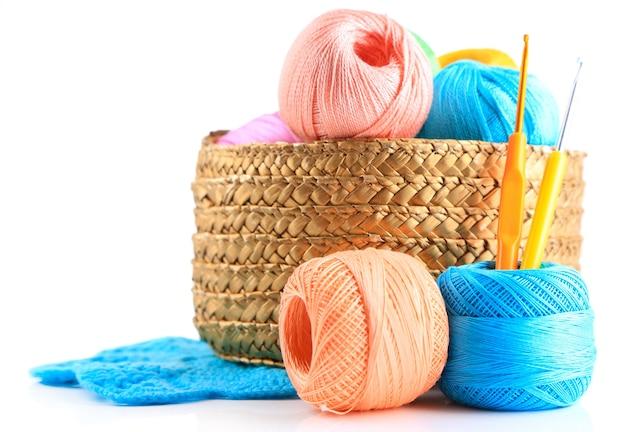 Filati colorati per maglieria con tovagliolo in cesto di vimini e uncinetto, isolato su bianco