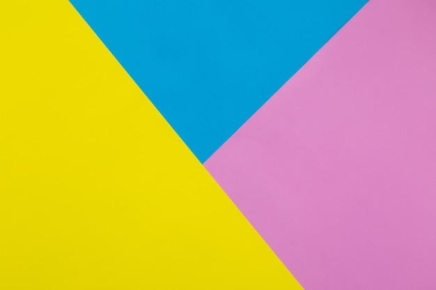 Priorità bassa di struttura della carta pastello colorata di giallo, blu e rosa, sfondo piatto geometrico laici.