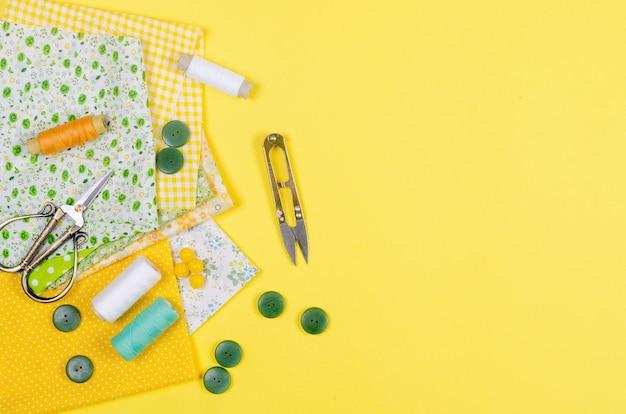 Tessuti colorati gialli e verdi, forbici, bottoni, rocchetti di filo e bicchieri su giallo