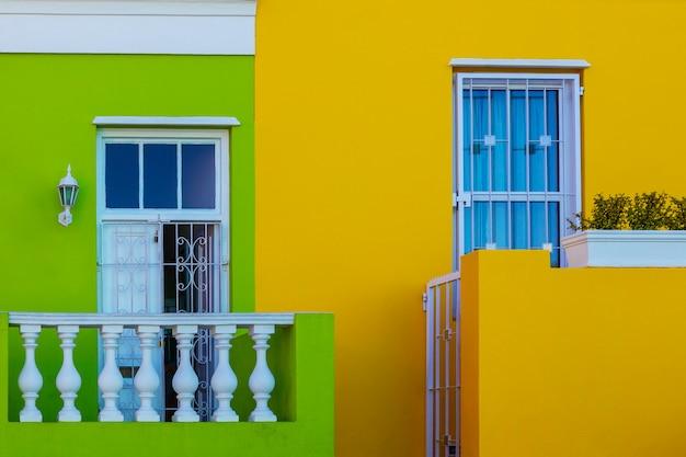 Facciata gialla e verde variopinta di vecchia casa nell'area di bo kaap, cape town