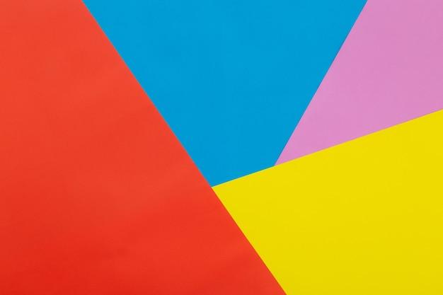 Priorità bassa di struttura della carta pastello colorata di giallo, arancione, blu e rosa, sfondo piatto geometrico laici.