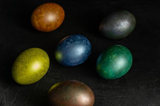 Colorfull marmo dipinto di uova di pasqua su sfondo nero. concetto di sfondo festivo minimo di pasqua.