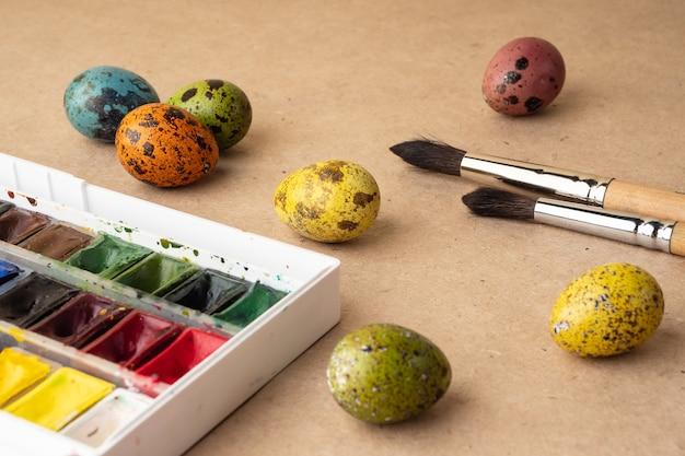 Uova da colorare per pasqua. vernici, pennelli, uova di quaglia su uno sfondo di lavorazione. preparazione per la celebrazione della pasqua, decorazioni per la festa, sfondo. concetto creativo.