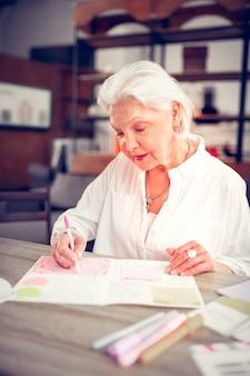 Colorare alcune immagini. signora anziana dai capelli grigi che indossa una camicetta bianca che colora alcune foto che hanno tempo libero