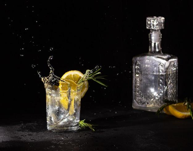Bevanda alcolica incolore in un bicchiere con una fetta di limone e rosmarino, splash