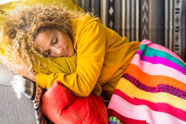 Colori e bel ritratto di donna adulta dormono e si rilassano a casa sul divano durante il giorno