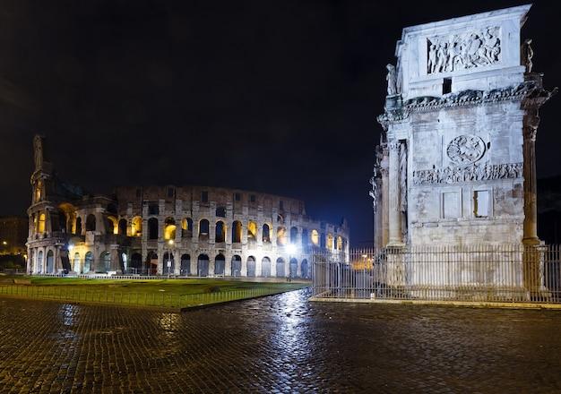 Vista notturna del colosseo e dell'arco di costantino a roma, italia