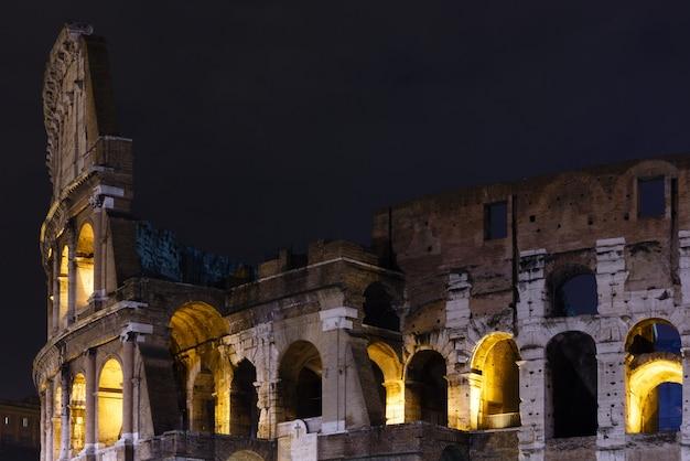 Vista notturna delle rovine del colosseo. il simbolo della roma imperiale, italia.