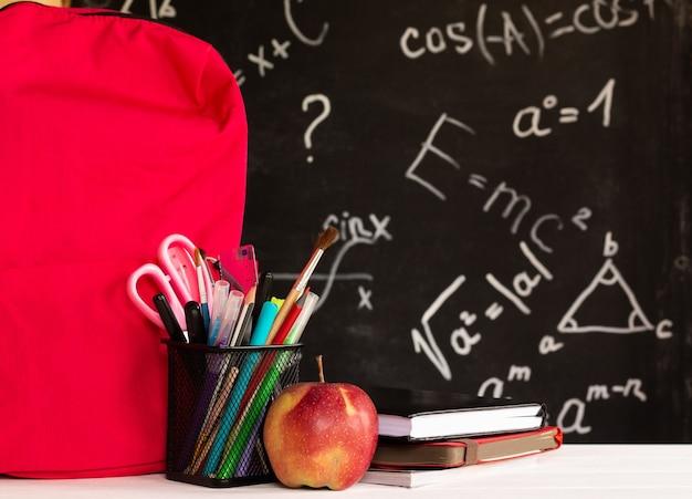 Materiale scolastico colorato, mela, libri, zaino su un controsoffitto bianco su sfondo lavagna con formule. concetto di educazione.