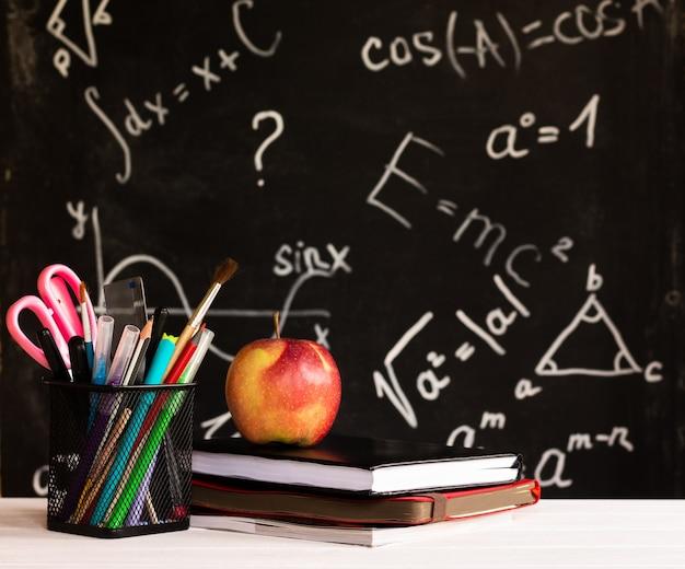Materiale scolastico colorato, mela, libri su controsoffitto bianco su sfondo lavagna con formule. concetto di educazione
