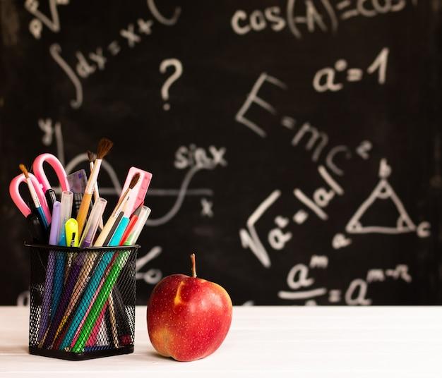 Materiale scolastico colorato e mela su controsoffitto in legno bianco su sfondo lavagna con formule. concetto di educazione