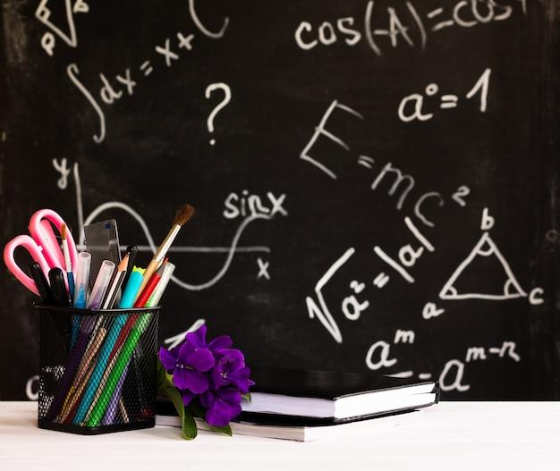 Materiale scolastico colorato, fiori, libri su un controsoffitto bianco su sfondo lavagna con formule. concetto di educazione
