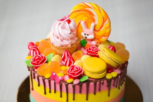 Torta colorata per la festa di compleanno di un bambino con lecca-lecca, caramelle, marmellata