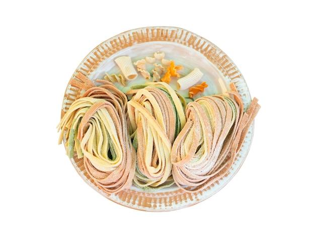 Tagliatella di pasta fresca colorata su piatto isolato su bianco