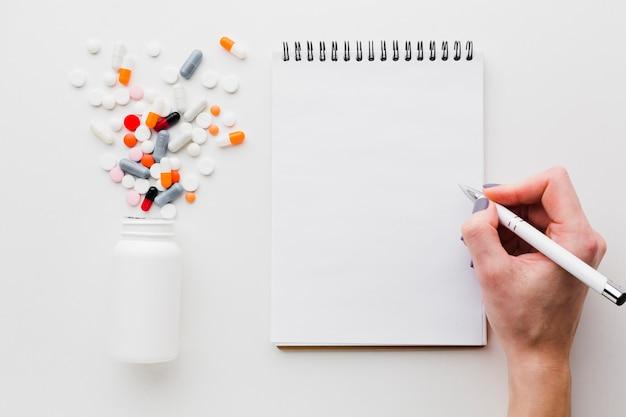 Pillole colorate versate dalla bottiglia di plastica e dal blocco note