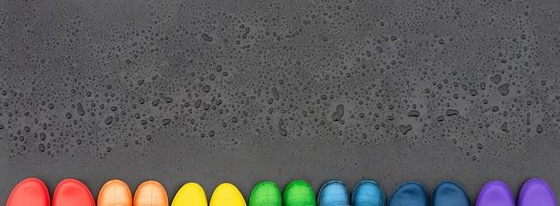 Stivali di gomma colorati rivestiti con colori arcobaleno sulla superficie nera di fronte a gocce di pioggia.