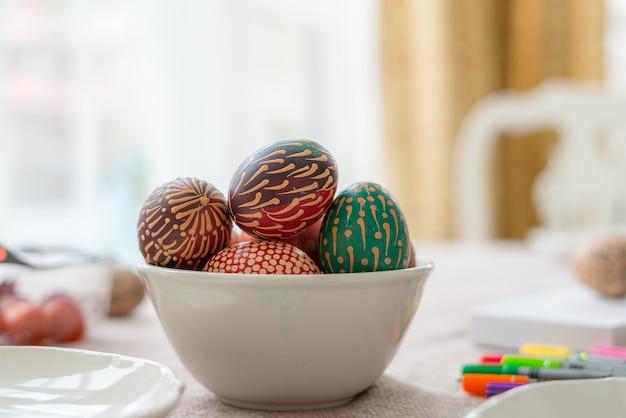 Uova di pasqua dipinte di cera colorata nella ciotola sulla tavola di legno
