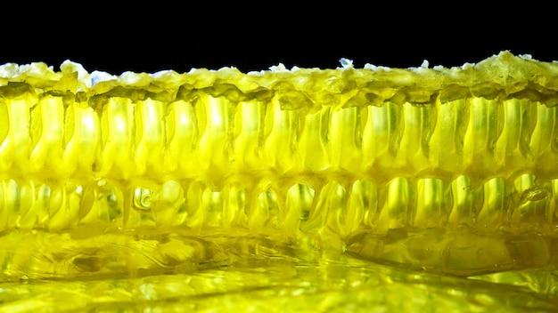 Il miele di favo si illumina su uno sfondo nero. dolce dolce. cibo ad alto contenuto calorico