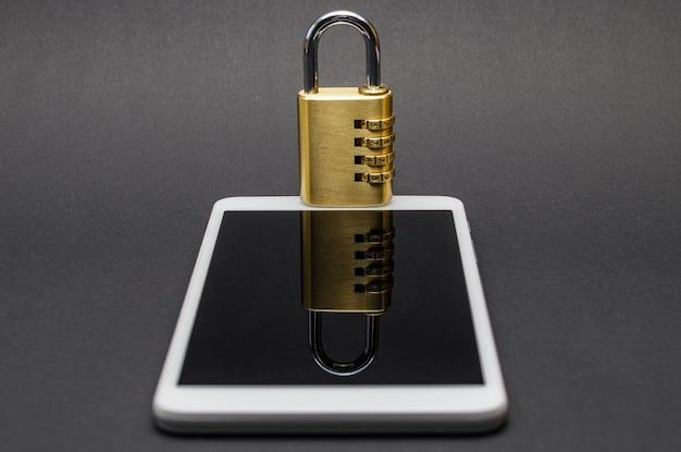 Il lucchetto a combinazione si trova sul dispositivo mobile e il suo riflesso è visibile. copia spazio