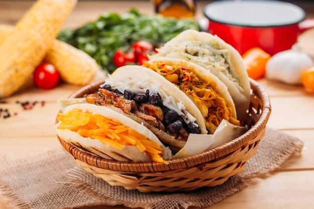 Combinazione delle tipiche arepas sudamericane in un cestino intrecciato