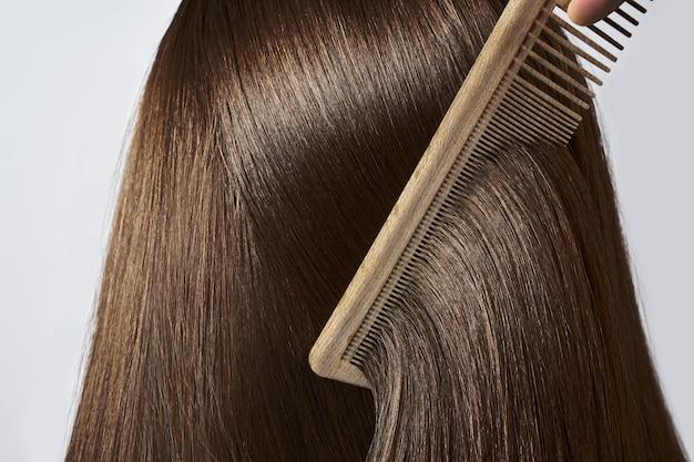 Pettinatura dei capelli femminili lunghi e lisci sani. avvicinamento
