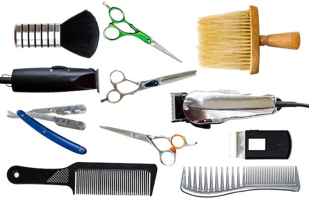 Pettini, clipper e altri strumenti di parrucchiere isolati su superficie bianca.